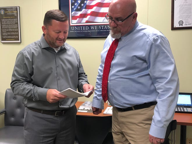 Wichita County Veterans Service Officer Tim Murdock, left, and Texas Veterans Commission counselor John Rollins review paperwork Monday in the Wichita County Veterans Office. The office will resume full-time hours beginning Tuesday, Oct. 15.