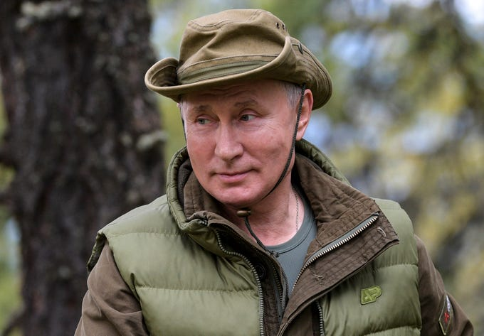 Vladimir Putin stands on a hill in Siberia.