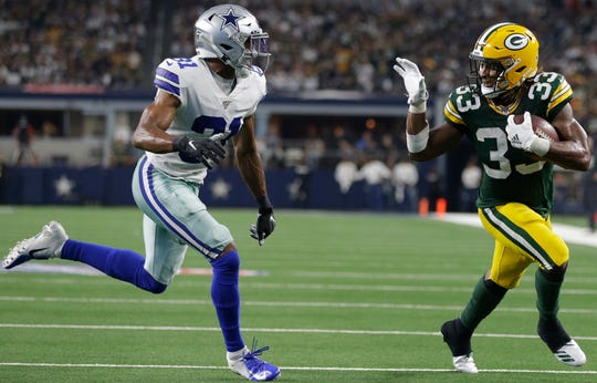 Aaron Jones waves to the Cowboys'  Byron Jones en route to scoring a touchdown.