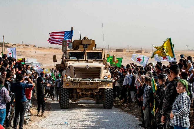 Syrian Kurds gather around a U.S. military vehicle on Oct. 6, 2019, near the Turkish border.
