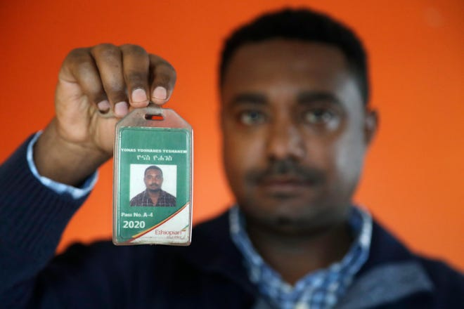 In this photo taken Sept. 24, 2019, Yonas Yeshanew, who resigned as Ethiopian Airline's chief engineer this summer and is seeking asylum in the U.S., poses with his company's identification card in the Seattle area.