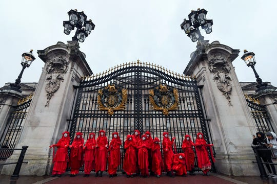 Climate activists pose for the media outside Buckingham Palace during an Extinction Rebellion protest in London on Oct. 7, 2019.