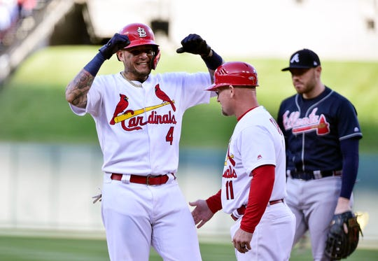 Yadier Molina celebrates with first base coach Stubby Clapp after hitting an RBI single in the eighth inning.