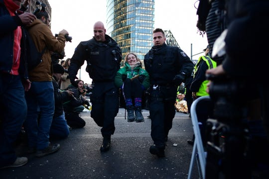 Police officers carry away an activist for the global environment movement Extinction Rebellion XR as they blocked the 'Potsdamer Platz' crossroads in Berlin, on October 7, 2019.