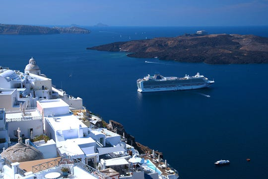 A cruise ship offers memorably fantastic views of the classic whitewashed villages of Santorini, Greece.
