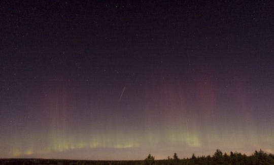 A Draconid meteor and the Northern Lights are observed near Skekarsbo, Sweden, about 90 miles north of Stockholm, on Oct. 8, 2011.