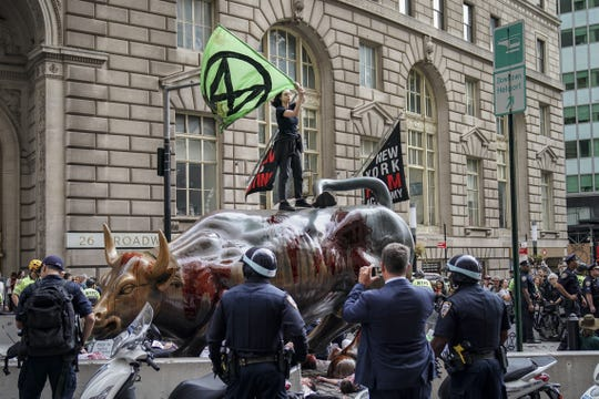 Environmental activists rally for action against climate change around the Wall Street Bull in the Financial District October 7, 2019 in New York City.