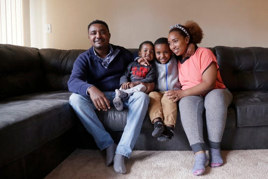 In this photo taken Sept. 24, 2019, Yonas Yeshanew, left, who resigned as Ethiopian Airline's chief engineer this summer and is seeking asylum in the U.S., poses with his family, including wife Tigist Hailu and sons Nathan Yonas, 1, and Yoel Yonas, 5, in the Seattle area.