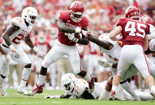Oklahoma running back Trey Sermon avoids a tackle attempt by the Texas defense during their game at the Cotton Bowl in 2018.