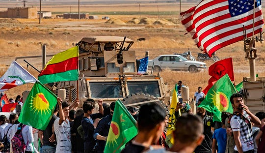 Syrian Kurds gather around a US armoured vehicle during a demonstration against Turkish threats next to a base for the US-led international coalition on the outskirts of Ras al-Ain town in Syria's Hasakeh province near the Turkish border on Oct. 6, 2019.