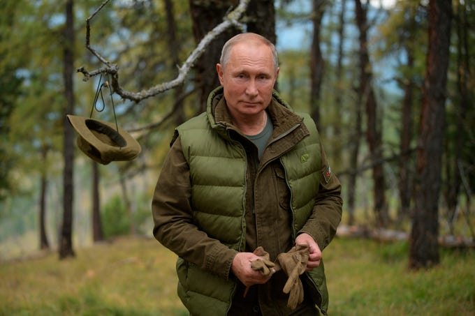 Vladimir Putin stands in southern Siberia's mountains.