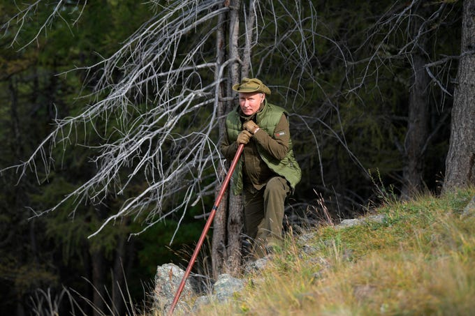 Vladimir Putin stands on a hill in southern Siberia's mountains during a break.