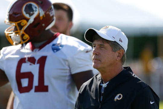 Washington Redskins offensive line coach Bill Callahan walks onto the field with Redskins offensive tackle Timon Parris (61) prior to practice on day one of training camp at Bon Secours Washington Redskins Training Center.