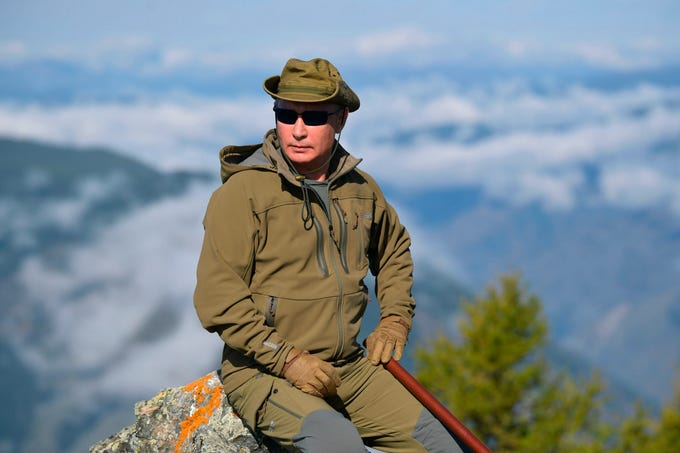 Russian President Vladimir Putin rests on a hill in Siberia during a break from state affairs ahead of his birthday. Russian president chose the Siberian taiga forest to go on a hike ahead of his birthday on Oct. 7.