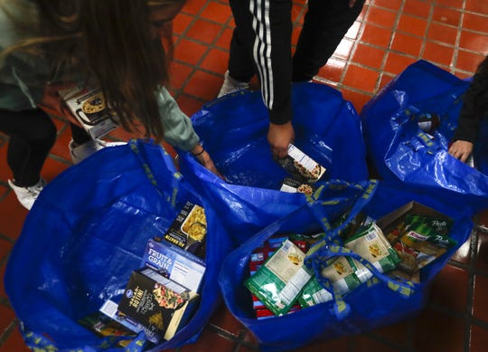 East students place food in bags for students struggling with food insecurity on Tuesday at Green Bay East High School.