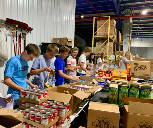 Volunteers sort food for the Sheboygan County Food Bank's Food For Thought backpack program. The program seeks to help kids struggling with food insecurity on weekends, when they don't have access to school food.
