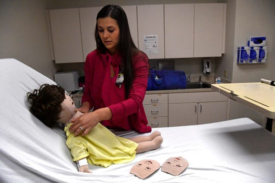 Drew Davis, a child life specialist, demonstrates Tuesday the unique doll she uses for teaching children about cancer treatments at Hendrick Medical Center. Beside the doll are cloth faces that attach using VELCRO-like fasteners for depicting emotional states.