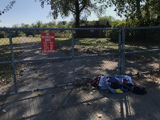 A pile of clothes sits outside the gate to one area of town where homeless camps pop up. The area was recently cleaned by several nonprofit organizations amid safety and sanitary concerns.