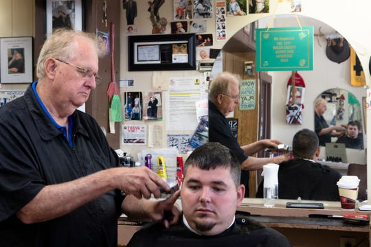 Josh Skidmore has his hair cut by Harold Montgomery, County Commissioner, at Montgomery's Barber Shop in Gallipolis, Ohio, on Thursday, Sept. 12, 2019. Montgomery is a long-time Republican county commissioner who supports Donald Trump.