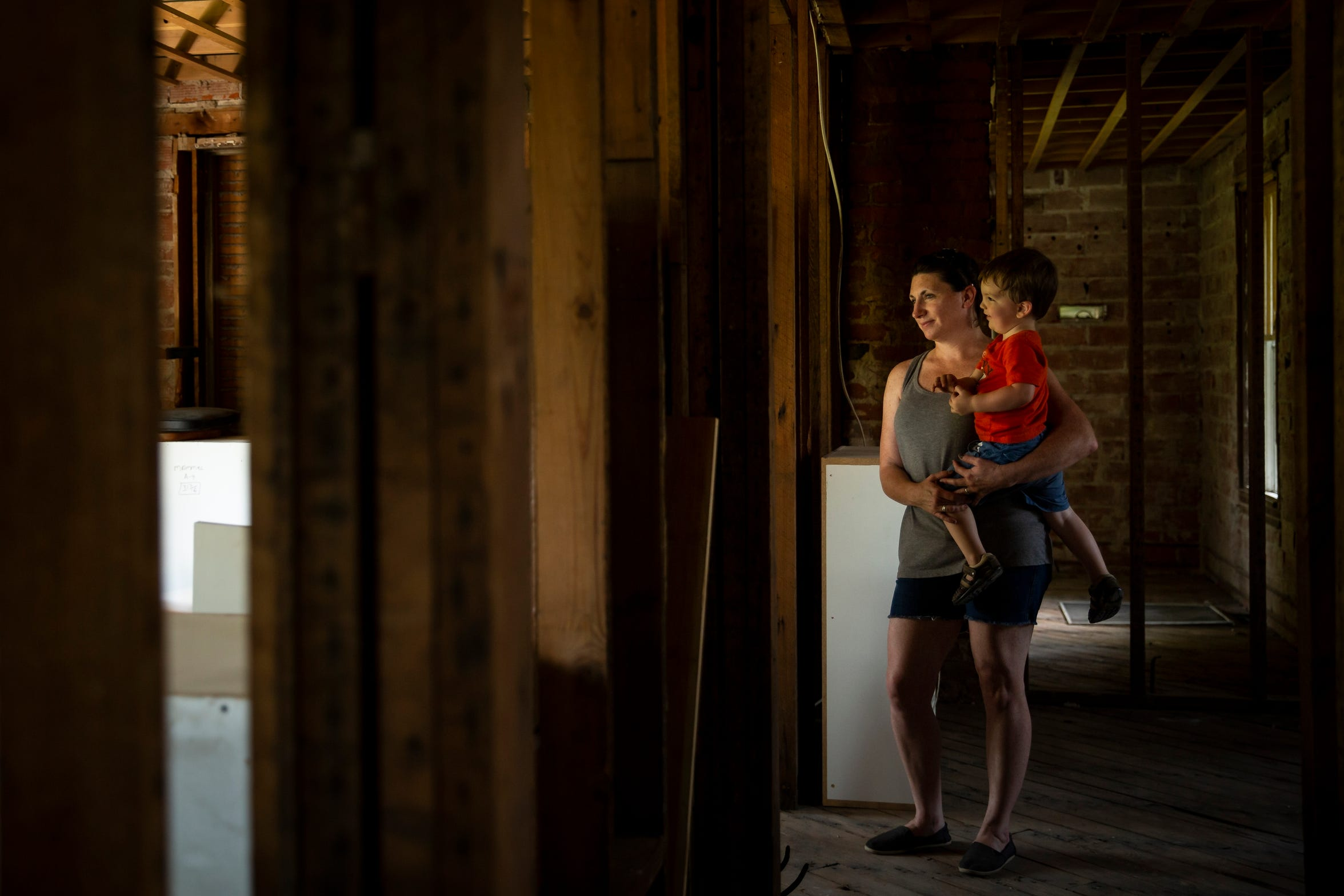 Amanda Tomlin holds her son in what's left of her flooded Hamburg home. The home was hit with 10 feet of water in March, just nine days after she, her husband and their two young sons moved in.