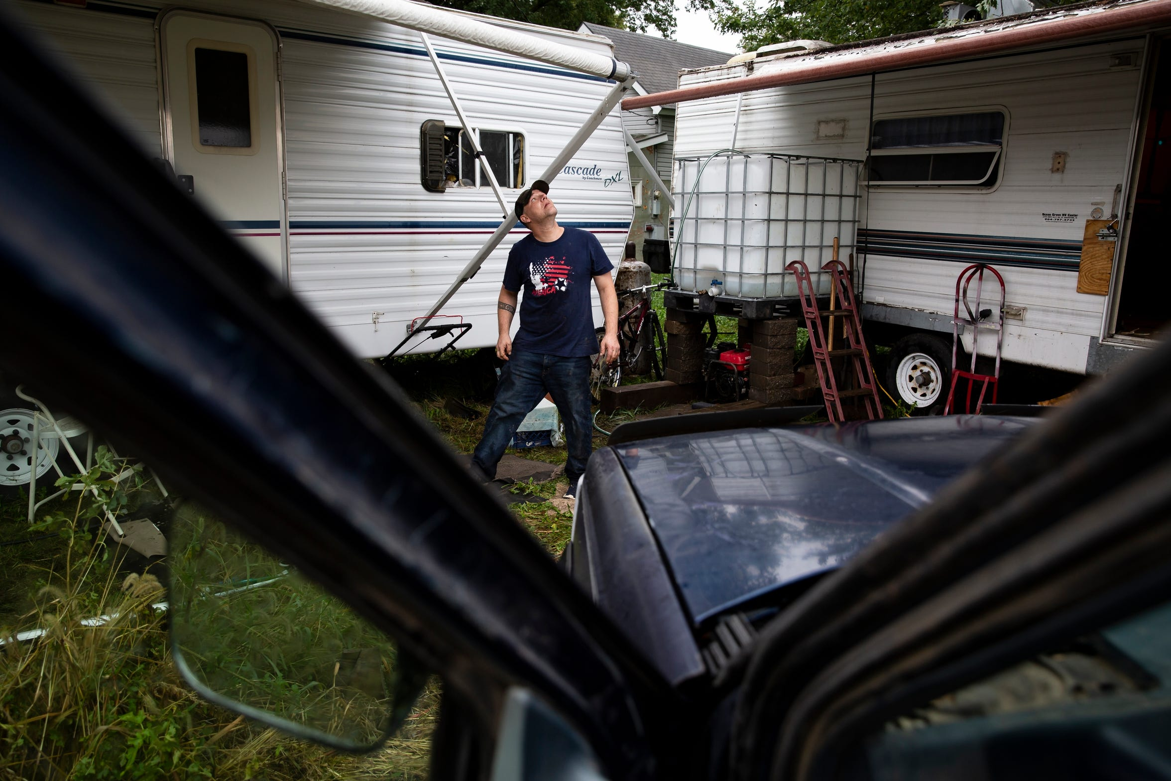 Matt Tyson, 39 of Pacific Junction, looks at the sky as rain begins to fall outside his trailer in Pacific Junction. Tyson and relatives lost their homes in the spring floods. He plans to spend the winter in his trailer as he helps them rebuild.