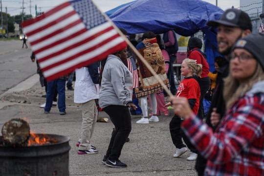 Flint Assembly worker DeÕAudtra Hunter-Randolph (left) dances with Isabella Collins as Collins joins her mother (not pictured) and other UAW members on the picket line along Van Slyke Rd. in Flint on Friday, October 4, 2019 outside of General Motors Flint Assembly as workers remain on strike from General Motors for the eighteenth day.