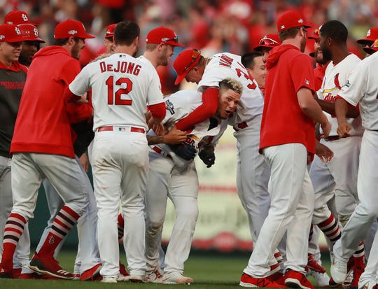 St. Louis Cardinals catcher Yadier Molina, center, is mobbed by teammates after hitting a winning sacrifice fly to score Kolten Wong and defeat the Atlanta Braves in the 10th inning of Game 4.