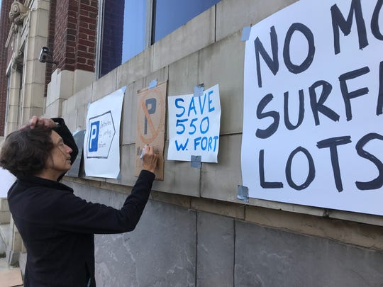 Maria Urquidi of Detroit colors in a sign at a protest Tuesday in front of the Saturday Night Building.