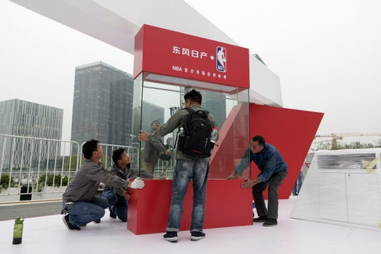 Workers dismantle signage for an NBA fan event scheduled to be held on Wednesday night at the Shanghai Oriental Sports Center in Shanghai, China on Tuesday. Chinese state broadcaster CCTV announced Tuesday it will no longer air two NBA preseason games set to be played in the country.