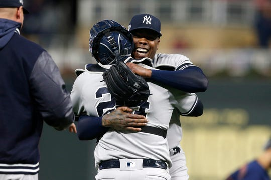 New York Yankees relief pitcher Aroldis Chapman, right, celebrates with teammate Gary Sanchez after their team's 5-1 victory over the Minnesota Twins in Game 3 Monday.