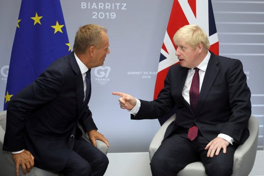 Britain's Prime Minister Boris Johnson, right, and President of the European Council Donald Tusk chat before an August meeting on the side of the G-7 summit in Biarritz, France.  Tusk directly addressed Johnson on Twitter Tuesday and gave him his fill about the fast-crumbling Brexit negotiations.