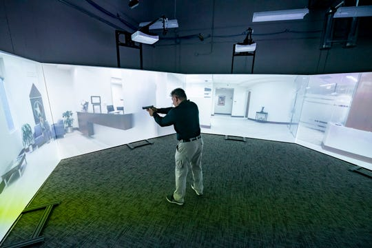 Police academy coordinator and firearms instructor David Schutz demonstrates the Firearms Training System at the Schoolcraft police academy training center, in Livonia.