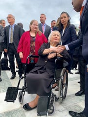 Michigan's Aimee Stephens, flanked by wife Donna at left and ACLU attorney Ria Tabacco Mar, greets well-wishers outside the U.S. Supreme Court on Tuesday after the justices heard arguments in her case. Rally-goers outside the court chanted her name as she left the building.
