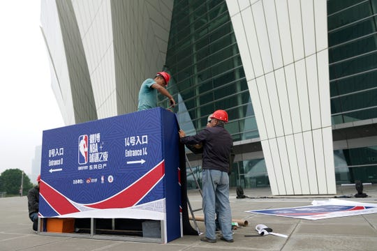 Workers dismantle signage for an NBA fan event scheduled to be held on Wednesday night at the Shanghai Oriental Sports Center in Shanghai, China, Tuesday, Oct. 8, 2019.