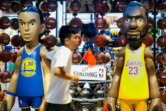 A man walks past statues of NBA players Stephen Curry of the Golden State Warriors, left, and Lebron James of the Los Angeles Lakers holding Chinese flags in the entrance of an NBA merchandise store in Beijing, Tuesday, Oct. 8, 2019.