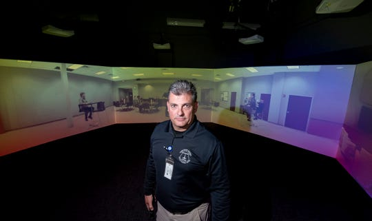 Police academy coordinator and firearms instructor David Schutz poses in front of the Firearms Training System at the Schoolcraft police academy training center, in Livonia.