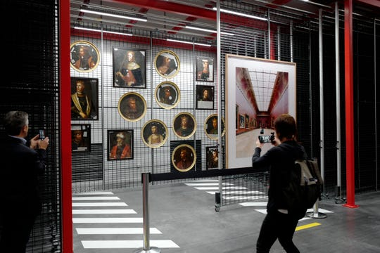 A person takes pictures of paintings at the Louvre Conservation Center, which was inaugurated in Lievin in northern France, Tuesday Oct.8, 2019.
