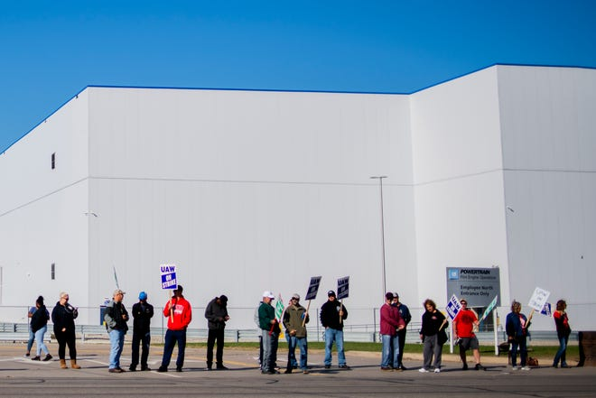 General Motors' Flint Assembly Plant employees line the street with picket signs in Flint on Monday.