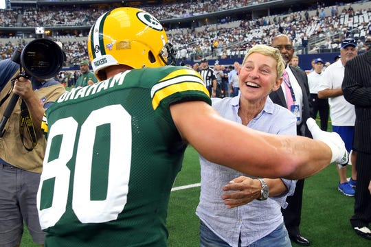 Jimmy Graham of the Green Bay Packers goes to hug Ellen DeGeneres before the game against the Dallas Cowboys at AT&T Stadium on Sunday in Arlington, Texas.