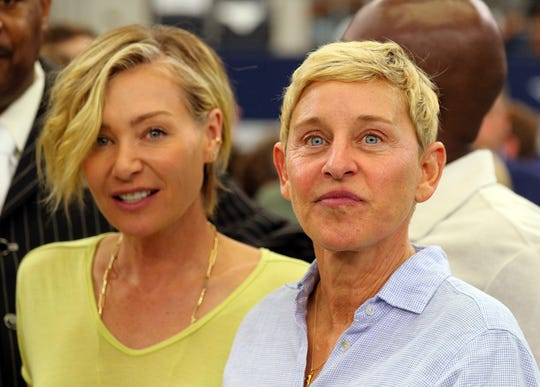 Portia de Rossi and Ellen DeGeneres watch the Green Bay Packers and Dallas Cowboys warm up before the game at AT&T Stadium on Sunday.