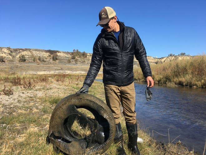 Friends of the Missouri River Breaks volunteer Conner Kelly holds up one of the five tires cleaned out of the river Sunday