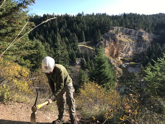 A volunteer with the Montana Wilderness Association wields a pulaski during a trail restoration project at Sluice Boxes State Park last Saturday