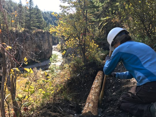 A volunteer with the Montana Wilderness Association installs a crib wall alone Overlook Trail at Sluice Boxes State Park