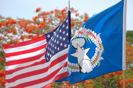 Flags of the United States and the Commonwealth of the Northern Mariana Islands, with flame trees in the background. President Trump declared a state of emergency for the CNMI because of Super Typhoon Hagibis, a year after Super Typhoon Yutu directly hit Saipan and Tinian in the CNMI.