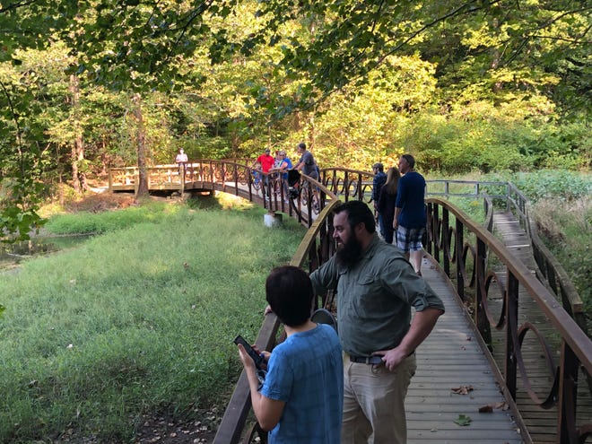 Pittsburg Tank & Tower staff and families gather on the bridge they built at Wilderness Lake in Audubon State Park.