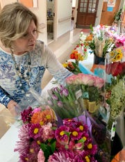 Liz Anderson of Ridgeland, a volunteer at Hospice Ministries, reaches for a flower to add to an arrangement for a patient's room.