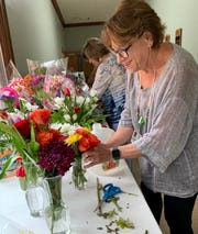 Joy Aycock of Jackson, a volunteer at Hospice Ministries, assembles a flower arrangement for a patient room