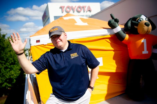 Local radio host Tyler Ivens of WNML waves to I-40 traffic from his tent atop Toyota Knoxville in West Knoxville, Tennessee on Tuesday, October 8, 2019. Ivens is camping on the roof of the car dealership until Tennessee wins its next game, which he is confident will happen Saturday when the Vols play Mississippi State.
