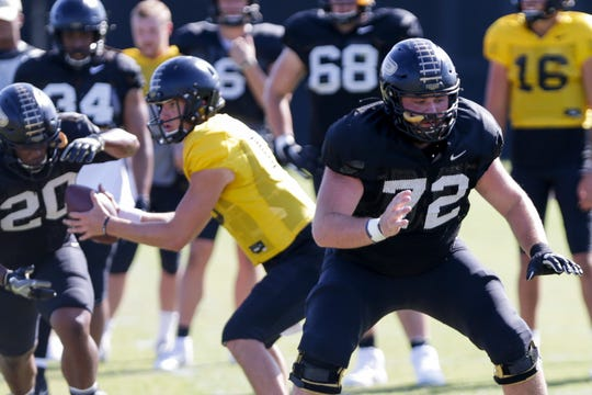 Purdue center Sam Garvin (72) blocks as Purdue quarterback Jack Plummer (13) hands the ball off to Purdue running back Alfred Armour (20) in the background during practice, Tuesday, Oct. 8, 2019 at Bimel Practice Complex in West Lafayette.