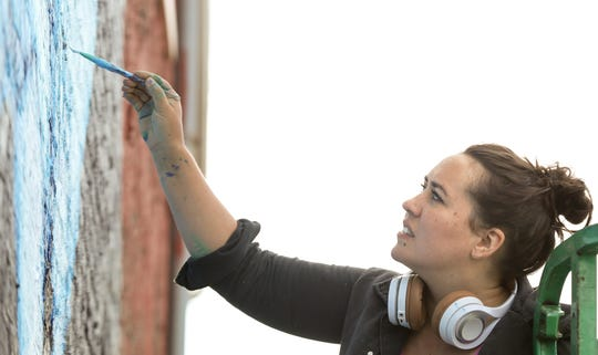 Liz Richter paints a mural in Smoketown at 900 East Shelby St. on Oct. 7, 2019.